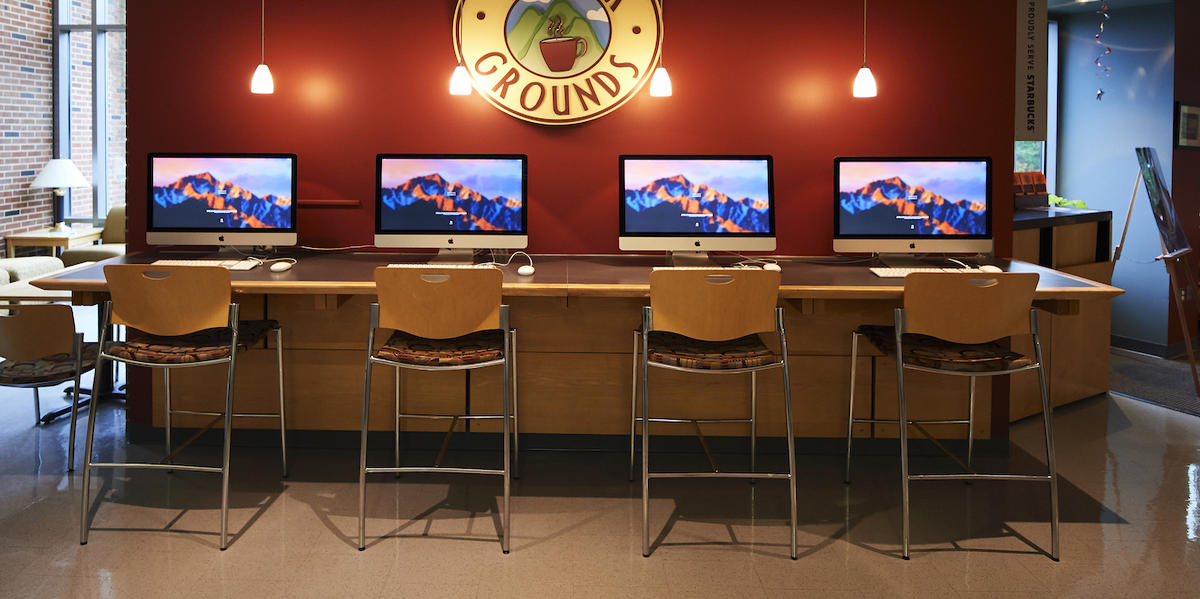 Four computer stations on a counter in front of the High Grounds circular logo