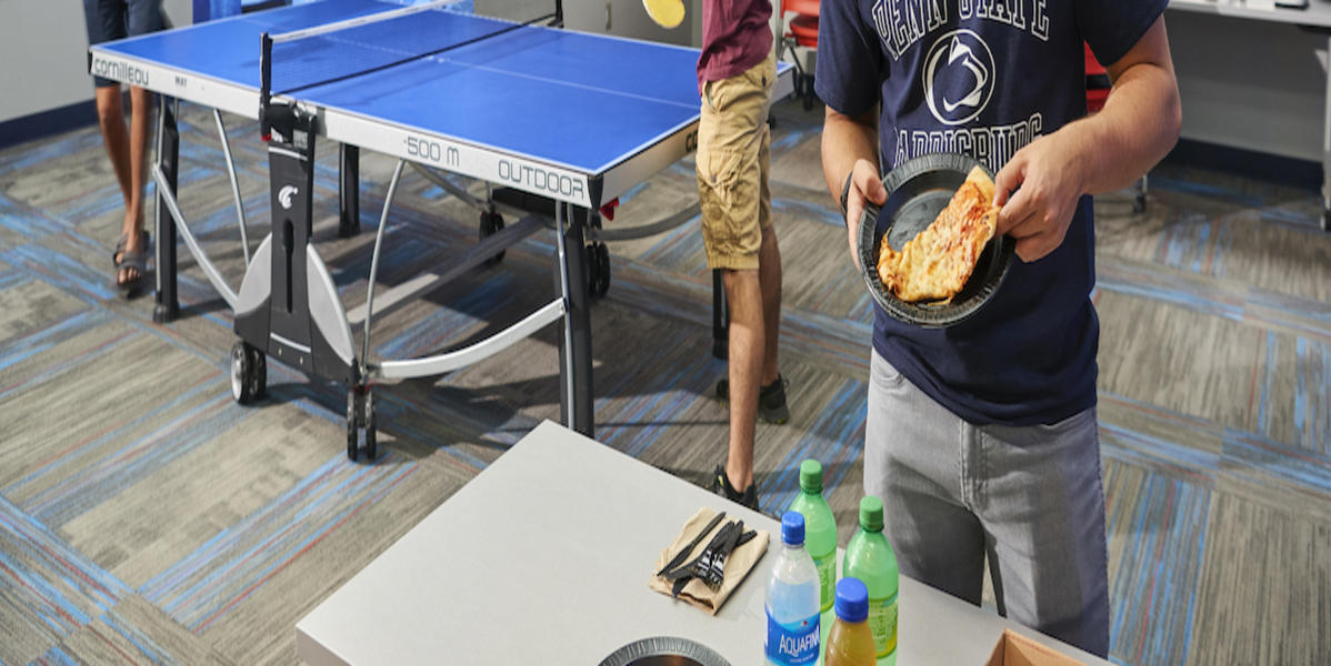 Male student poses with a piece of pizza while two students play ping pong in the background